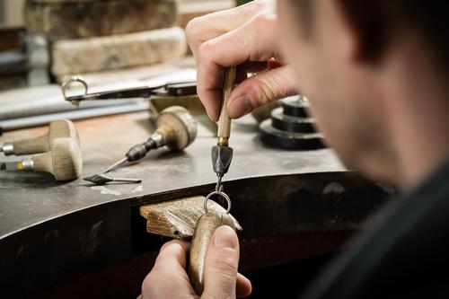 Goldschmied stellt Goldring her und setzt Diamanten in Werkstatt ein.
